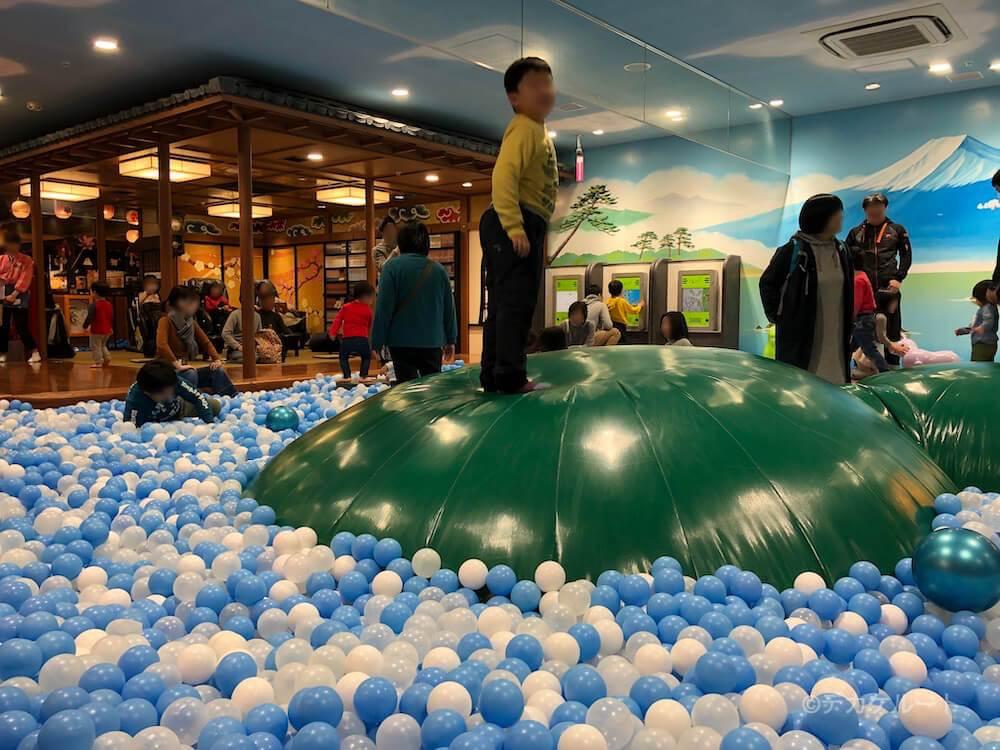 空気が入った「浮島」に乗って遊ぶ男の子(こどもの湯のボールプール)